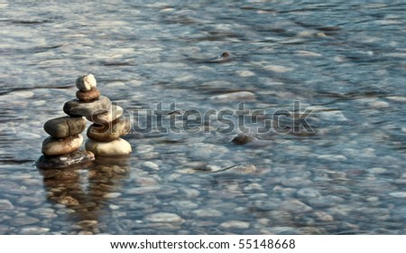 tranquility concept - pebble pyramid in a river - stock photo