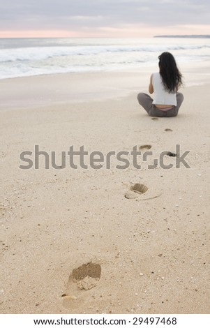 Tranquility meditation scene. Young female doing yoga on a quiet yellow sand beach - stock photo