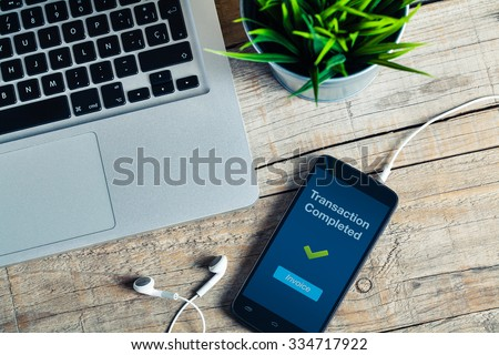 Transaction Completed message on smart phone screen. Detail of workplace. - stock photo