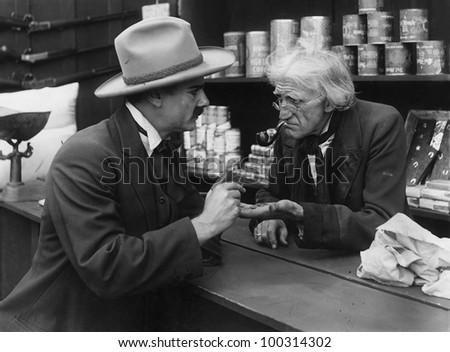 Transaction with elderly shopkeeper - stock photo
