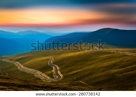 Transalpina road. Transalpina is one of the highest roads passing the Carpathians in Romania. Layers of haze cover the mountains peaks at sunset. - stock photo