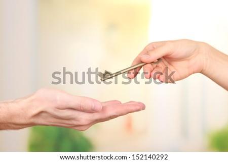 Transfer of house key, on bright background - stock photo
