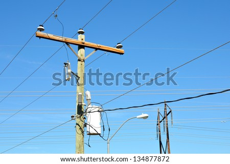 Transformers on an electrical post and multiple powerlines - stock photo