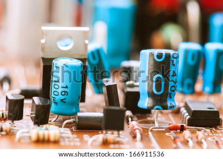 transistors capacitors resistors and other electronic components mounted on motherboard - stock photo