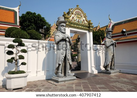 TRANSITION GATE WITH STATUE Temple transition gate decorate with relief art and two stone warrior statues.  - stock photo