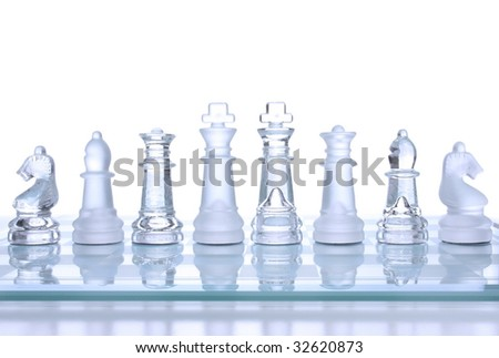 Translucent glass chess figures on a board