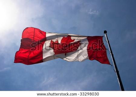 Translucent large Canada flag against blue sky - stock photo
