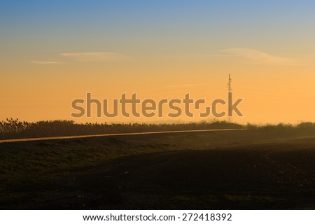 Transmission power lines tower by the railroad in the early morning.  - stock photo