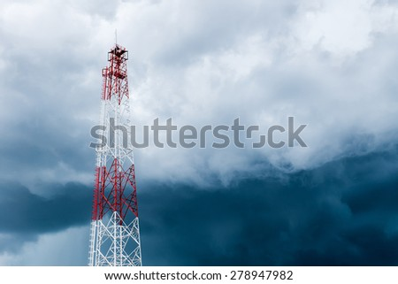transmission tower against storm clouds - stock photo