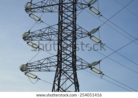 Transmission tower cage with power lines. High voltage smart electric grid infrastructure. Power cables providing public utility service.
