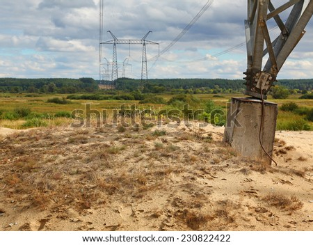 Transmission tower through the valley of the summer day - stock photo