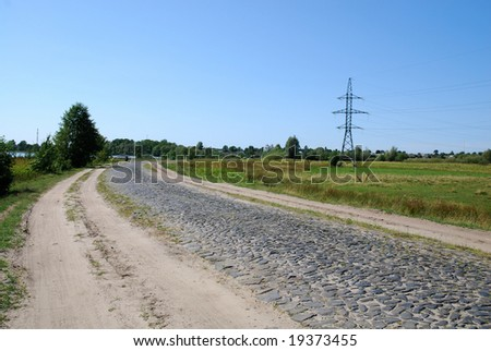 Transmitter tower in green field on sunny day - stock photo