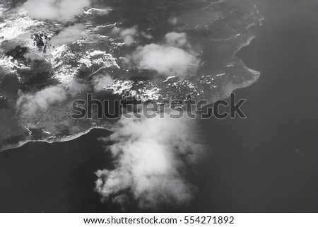 Transoceanic flights. Pacific ocean and Kamchatka (Russia) from height of bird flight. View from plane on East coast, mountains drop into sea. Black-and-white photograph