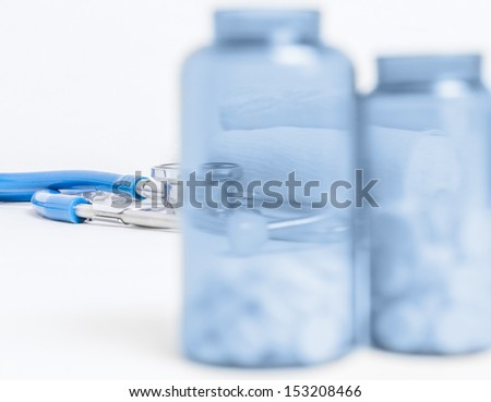 Transparent bottle of pills on the background of the stethoscope
