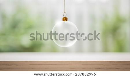 Transparent Christmas ball over wood table - stock photo