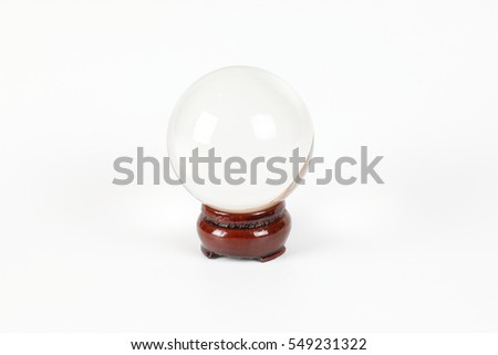 Transparent crystal ball on wooden stand white background