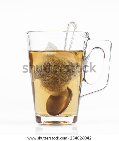 Transparent cup of tea with tea bag and spoon on white background.
