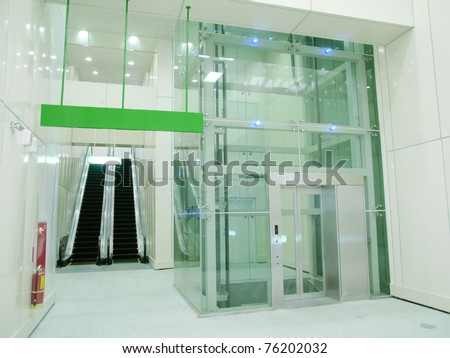Transparent elevator in underground passage - stock photo