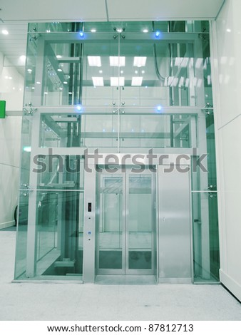 Transparent elevator in underground passage - stock photo
