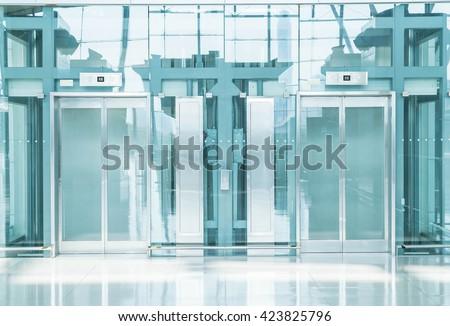 Transparent elevator in underground passage - blue white balance processing - stock photo