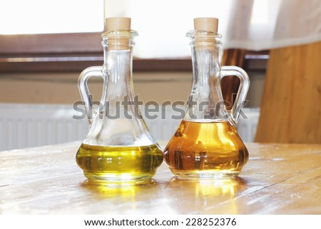transparent glass bottles of olive oil and vinegar on a wooden table - stock photo