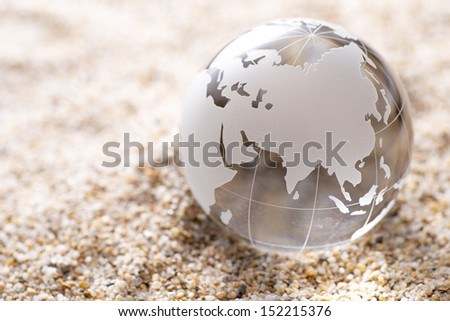 Transparent glass globe on sand background - stock photo