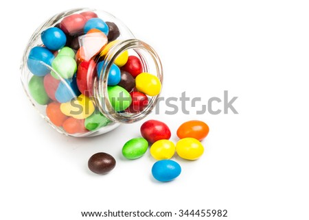 Transparent glass jar with colorful chocolate coated candies on white background - stock photo