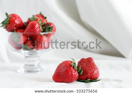 Transparent glass vase full of red strawberries on white textile background with free space for text