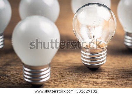 Transparent light bulb glowing among the white light bulbs