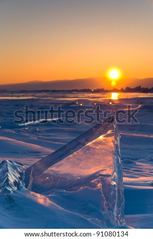 Transparent piece of ice on  surface of frozen lake. Low depth-in view. - stock photo