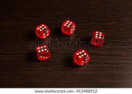 transparent red dices against a dark wooden table