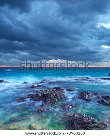Transparent sea with stone on background dark sky - stock photo