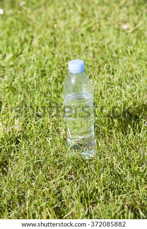 transparent small plastic water bottle with blue cap on green lawn outdoor - stock photo