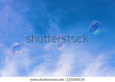 Transparent soap bubbles in the sky - stock photo