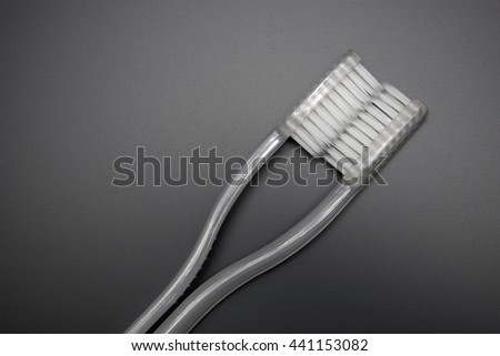 Transparent white toothbrushes on blackboard background. Space for texts. - stock photo