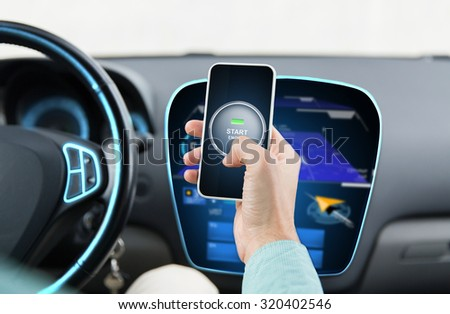 transport, business trip, technology and people concept - close up of male hands with start engine button on smart phone screen in car - stock photo