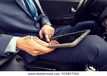 transport, business trip, technology and people concept -close up of young man with tablet pc computer driving car - stock photo