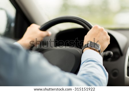 transport, business trip, technology, time and people concept - close up of man with wristwatch driving car - stock photo