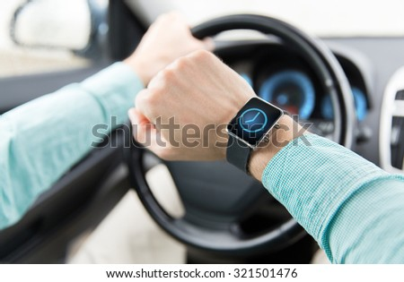 transport, business trip, technology, time and people concept - close up of man with wristwatch or smart watch driving car - stock photo