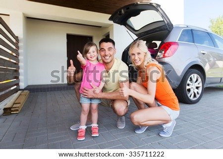 transport, leisure, road trip and people concept - happy  family with little girl and hatchback car showing thumbs up at home parking space