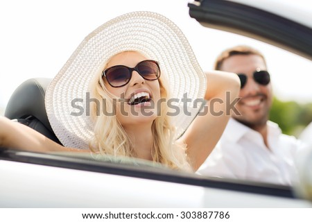 transport, leisure, road trip and people concept - happy man and woman driving in cabriolet car outdoors - stock photo