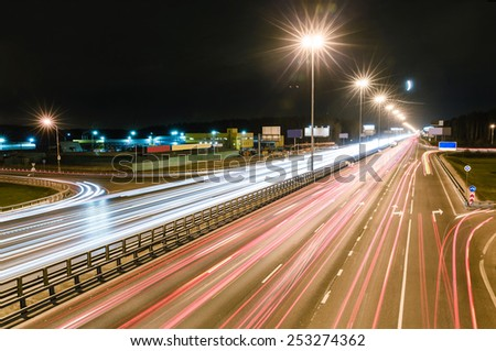 transport metropolis, traffic and blurry lights of cars on multi-lane highways and dense road traffic at night in Moscow