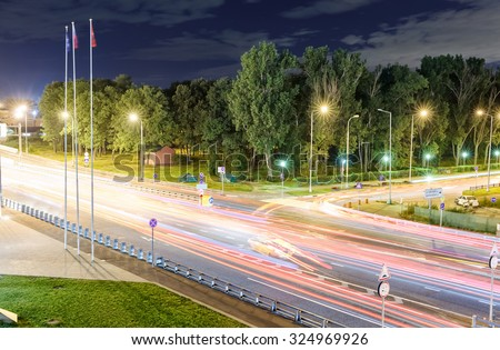 transport metropolis, traffic and blurry lights of cars on multi-lane highways and dense road traffic at night in Moscow at summer - stock photo