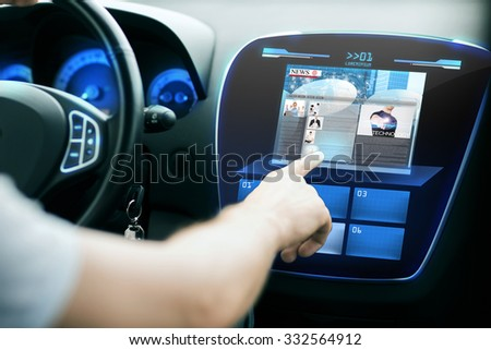 transport, modern technology, mass media and people concept - male hand pointing finger to monitor on car panel and reading news - stock photo
