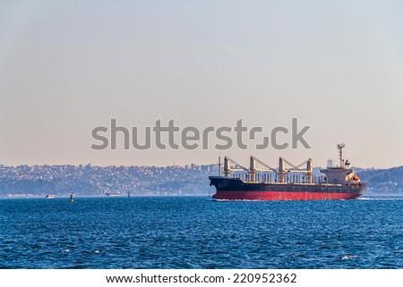 Transport ship sails Bosphorus on sunny autumn day. - stock photo