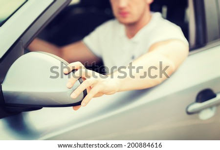 transportation and vehicle concept - man ajusting rear view mirror - stock photo
