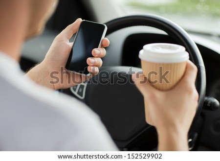 transportation and vehicle concept - man drinking coffee and using phone while driving the car - stock photo