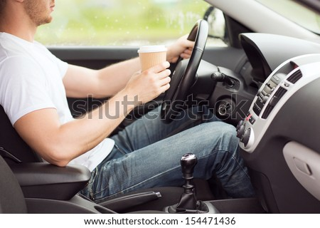 transportation and vehicle concept - man drinking coffee while driving the car - stock photo