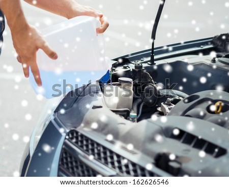 transportation and vehicle concept - man opening car bonnet and filling windscreen water tank with washing liquid - stock photo