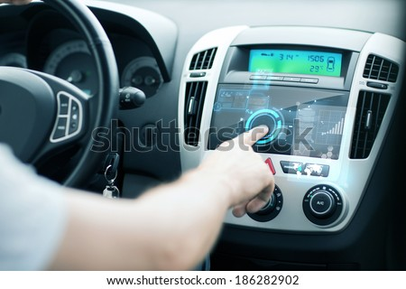 transportation and vehicle concept - man using car control panel - stock photo